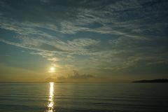 Sonnenuntergang und Sonnenaufgang mit drastischem Himmel über Ozean stockbild