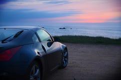 Sonnenuntergang und Sport-Auto stockfoto
