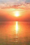 Sonnenuntergang und Wolken auf einem See Lizenzfreie Stockbilder