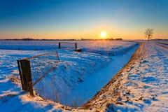 Sonnenuntergang und Zaun mit Wiese im Winter Lizenzfreie Stockfotografie