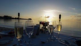 Sonnenuntergangabendessen auf einem Strand bei Sonnenuntergang mit tiki beleuchtet bei Sonnenuntergang Lizenzfreies Stockfoto