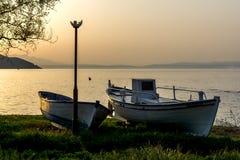 Sonnenuntergangansicht über Damm und alte Boote in Thassos-Stadt, Griechenland Stockfoto