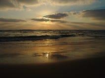 Sonnenuntergangansicht über einen ruhigen sandigen Strand mit bewölktem Himmel und goldenem Licht stockbild