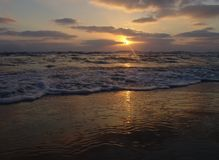 Sonnenuntergangansicht über einen ruhigen sandigen Strand mit bewölktem Himmel und goldenem Licht lizenzfreies stockfoto