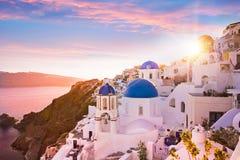 Sonnenuntergangansicht der blauen Haubenkirchen von Santorini, Griechenland Stockfotos