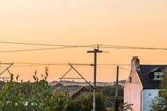 Sonnenuntergangansicht-Livedrähte über BRITISCHER Eisenbahn nahe bei counryside Haus in England stockfoto