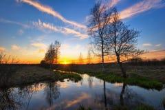 Sonnenuntergangfeld mit Fluss Lizenzfreie Stockbilder