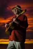 Sonnenunterganggitarrist mit drastischer Beleuchtung Lizenzfreie Stockfotos
