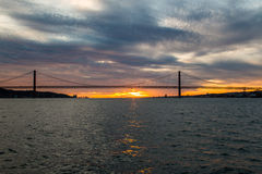 Sonnenunterganghimmel über dem Tajo, überbrücken am 25. April Lissabon und tragen von am Schiff, Portugal Lizenzfreie Stockfotografie