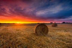 Sonnenunterganghimmel über Feld mit Strohballen Stockfotos