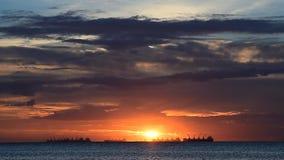 Sonnenunterganghimmel in Meer mit Frachtschiffschattenbildern stock footage