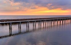 Sonnenunterganghimmel, Reihen von Bambusstöcken im Meer und Zementbrücke nahe Matchanu-Schrein, Phanthai Norasing, Bezirk Mueang  Lizenzfreie Stockfotos
