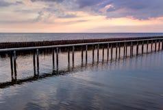 Sonnenunterganghimmel, Reihen von Bambusstöcken im Meer und Zementbrücke nahe Matchanu-Schrein, Phanthai Norasing, Bezirk Mueang  Stockfoto