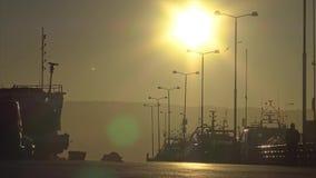Sonnenunterganghintergrundbeleuchtung auf dem Hafen der kleinen spanischen Stadt Palamos, Spanien stock video footage