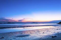 Sonnenuntergangküste mit Reflexion der Wolken Lizenzfreie Stockfotos
