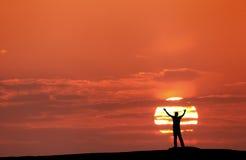 Sonnenunterganglandschaft mit Schattenbild eines Mannes mit den angehobenen-oben Armen Stockbild