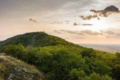 Sonnenunterganglandschaftspanorama, Hügel in der goldenen Stunde, kleines Dorf im Tal, schöne Farben und Wolken Lizenzfreie Stockbilder