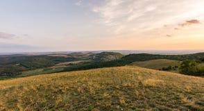 Sonnenunterganglandschaftspanorama, Hügel in der goldenen Stunde, kleines Dorf im Tal, schöne Farben und Wolken Lizenzfreies Stockfoto