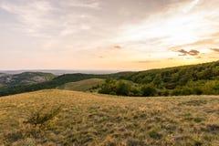 Sonnenunterganglandschaftspanorama, Hügel in der goldenen Stunde, kleines Dorf im Tal, schöne Farben und Wolken Stockfotografie