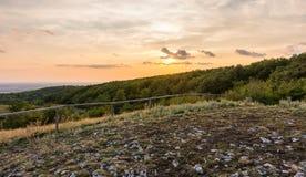 Sonnenunterganglandschaftspanorama, Hügel in der goldenen Stunde, kleines Dorf im Tal, schöne Farben und Wolken Stockfoto