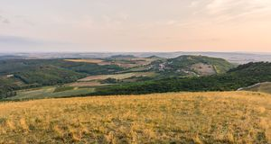 Sonnenunterganglandschaftspanorama, Hügel in der goldenen Stunde, kleines Dorf im Tal, schöne Farben und Wolken Lizenzfreie Stockfotografie