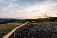 Sonnenunterganglandschaftspanorama, Hügel in der goldenen Stunde, kleines Dorf im Tal, schöne Farben und Wolken Lizenzfreie Stockfotos