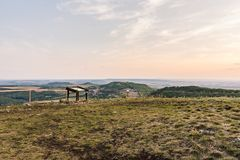 Sonnenunterganglandschaftspanorama, Hügel in der goldenen Stunde, kleines Dorf im Tal, schöne Farben und Wolken Lizenzfreies Stockbild