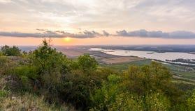 Sonnenunterganglandschaftspanorama, Hügel in der goldenen Stunde, kleines Dorf im Tal, schöne Farben und Wolken Stockbild