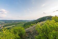 Sonnenunterganglandschaftspanorama, Hügel in der goldenen Stunde, kleines Dorf im Tal, schöne Farben und Wolken Stockfotos