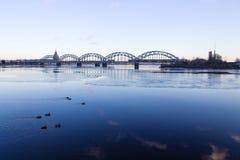 Sonnenunterganglicht über Brücke und Fluss in Riga Stockbild