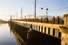Sonnenunterganglicht über Brücke und Fluss in Riga Stockbilder