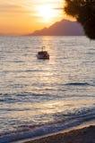 Sonnenuntergangmotorboot auf dem adriatisches Seestrand in Makarska, Kroatien Stockbilder