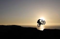 Sonnenuntergangradfahrerspringen Stockfoto