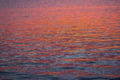 Sonnenuntergangreflexion auf ruhigen Meereswogen Stockfotos