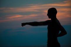 Sonnenuntergangschattenbild von übenden Kampfkünsten des Mannes Stockbild