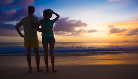 Sonnenuntergangschattenbild von jungen Paaren in der Liebe am Strand Stockfotos