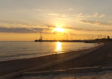Sonnenuntergangsonnenlichtstrand-Stadtfischer, die im Ufer fischen Stockfoto