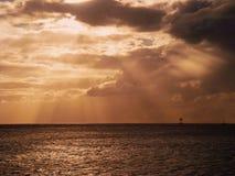 Sonnenuntergangsonnenstrahlen und -wolken in dem Ozean stockbild