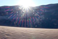 Sonnenuntergangstrahlen über Sanddünen und Bergen Stockbilder