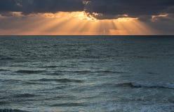 Sonnenuntergangstrahlen über Ozean Stockfotos