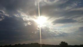 Sonnenuntergangstrahlen, die unten aus den Wolken heraus schlagen Stockbilder