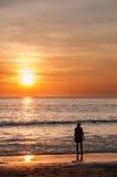Sonnenuntergangstrand mit einer jungen Frau Stockbild