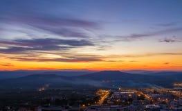 Sonnenuntergangszene mit Bergen im Hintergrund und Stadt Matera im Vordergrund, industrielle Ansicht Lizenzfreie Stockfotos