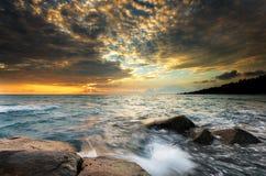 Sonnenuntergangwellenfelsen auf dem Strand Stockbild