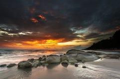 Sonnenuntergangwellenfelsen-Strandhintergrund Stockfotografie