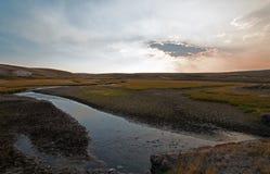 Sonnenuntergangwolkensonne strahlt an Elche Anter-Nebenfluss in Hayden Valley in Yellowstone Nationalpark in Wyoming aus Stockfotografie