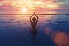 Sonnenuntergangyogafrau auf Meer-coastMeditate Stockbild