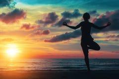 Sonnenuntergangyogafrau auf Ozeanküste entspannen sich Stockfoto