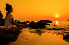 Sonnenuntergangyogafrau mit Geistigkeit auf Seeküste Lizenzfreie Stockfotografie