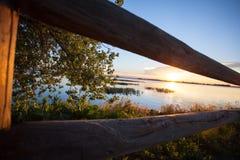 Sonnenuntergangzaunbaum und -see Lizenzfreies Stockfoto